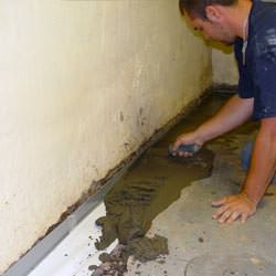 A basement waterproofer installing a perimeter drain system in Emporium