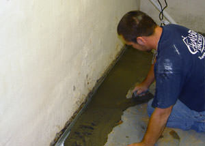 Restoring a concrete slab floor with fresh concrete after jackhammering it and installing a drain system in Bellwood.